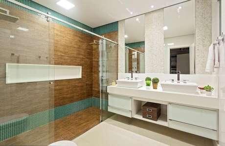 13. Banheiro amplo decorado com revestimento que imita madeira dentro do box e pastilhas de vidro verde – Foto: Laura Santos