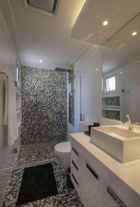 31. Decoração para banheiro branco com pastilhas de vidro no piso e parede dentro do box – Foto: Érica Salgueiro