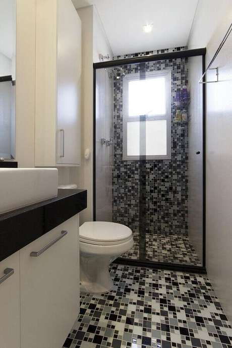 32. Banheiro com pastilhas de vidro preto e branco com decoração simples – Foto: Juliana Conforto
