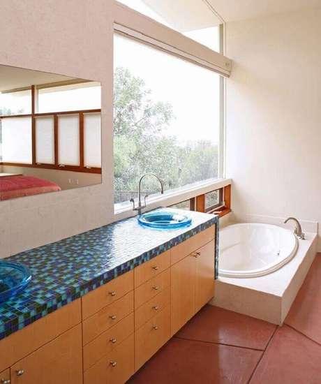 36. Decoração simples para banheiro com banheira e pastilhas de vidro azul na bancada – Foto: Tracy Stone Aia