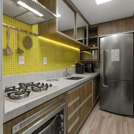 46. Pastilhas de vidro amarela para decoração de cozinha com armários de madeira e cooktop – Foto: Anna Arquitetura