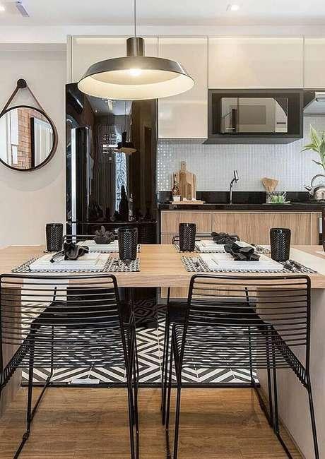 52. Pastilhas de vidro para cozinha com geladeira preta e bancada de madeira com cadeiras modernas – Foto: Pinterest