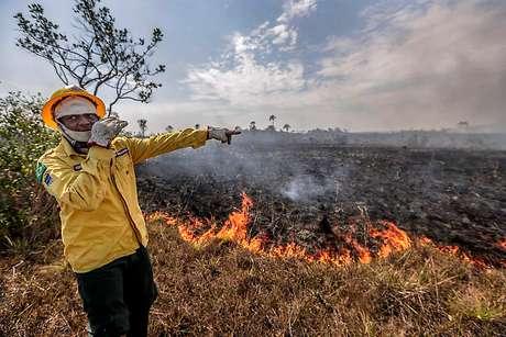 Em frente ao fogo, brigadista conversa com colegas