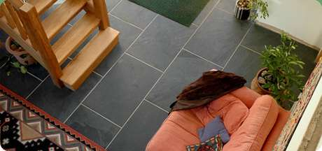 2. Piso ardósia em casa com sofá coral e tapete colorido – Por: Pinterest