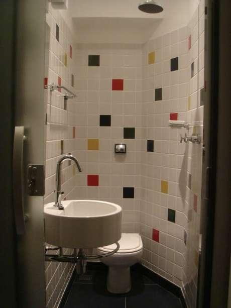 56. Banheiro coberto com azulejos brancos e coloridos. Projeto de Andre Martins