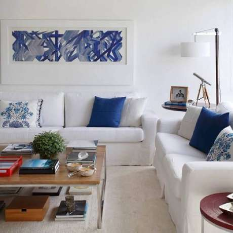 15. A decoração com sofá branco e almofadas azuis garante a sala um toque suave na decoração – Foto: Adriana Vale Patricia Carvalho
