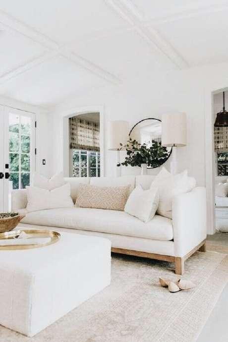 16. Decoração clean para sala com sofá branco e espelho redondo – Foto: American Home