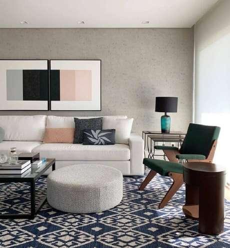21. Decoração moderna para sala com sofá branco e parede de cimento queimado com quadro grande – Foto: Paula Magnani