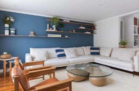 5. Decoração com poltronas de madeira e sofá de canto branco para sala ampla com paredes azuis – Foto: Voa Arquitetura