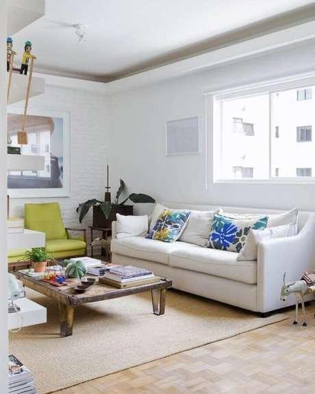 28. Invista em detalhes coloridos na sala de estar decorada com sofá branco de couro – Foto: Reedecore