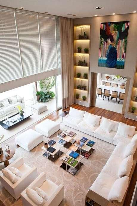 1. Decoração em tons neutros para sala ampla com sofá de canto branco combinando com as poltronas e puffs – Foto: Pinterest