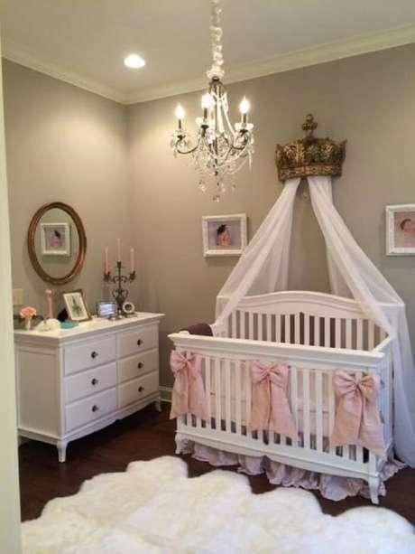 52. Quarto de bebê menina com cômoda branca, tapete felpudo e dossel fixado por uma coroa. Fonte: Pinterest
