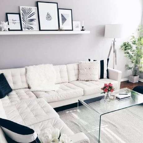 31. Sofá de canto branco para decoração de sala clena com mesa de centro de acrílico e quadros apoiados em prateleira estreita – Foto: Pinterest