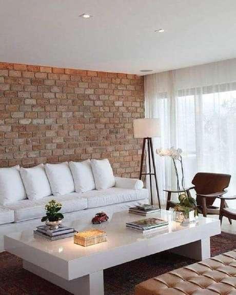 33. Sala de estar decorada com parede de tijolinho e sofá branco – Foto: Ideias Decor