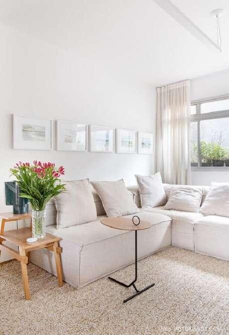37. Sala decorada com sofá de canto branco e mesa lateral de madeira – Foto: Histórias de Casa