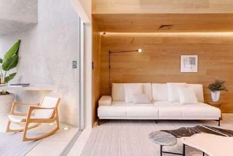 41. Sala integrada com varanda decorada com revestimento de madeira e sofá branco moderno – Foto: Suite Arquitetos