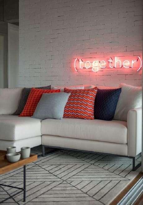 43. Sala moderna decorada com sofá branco, almofadas coloridas e luminária neon em parede de tijolinho branco – Foto: Casa de Valentina
