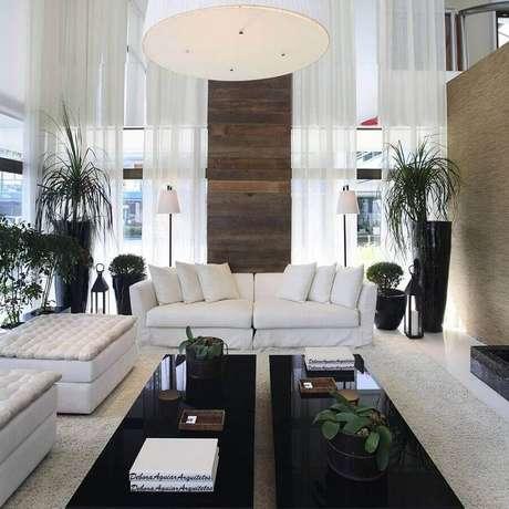 46. Sala sofisticada decorada com sofá branco e mesas de centro pretas – Foto: Assetproject