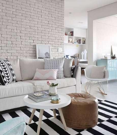 49. Sofá branco decorado com parede de tijolinhos brancos e puff redondo de couro – Foto: Assetproject