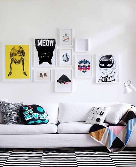 50. Sala decorada com sofá branco, quadrinhos decorativos e almofadas divertidas – Foto: Assetproject