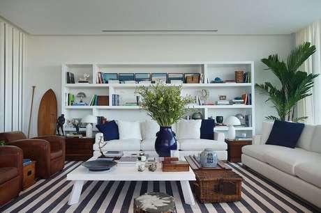 52. Sala ampla decorada com sofá branco, tapete listrado e poltronas de couro – Foto: Radar Design
