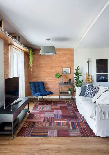 56. Sofá branco para sala de estar decorada com parede de tijolinho e tapete estampado – Foto: Casa de Valentina