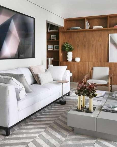 57. Sofá branco para sala de estar decorada com tapete cinza e estante de madeira – Foto: Simone Saccab – Arquiteta