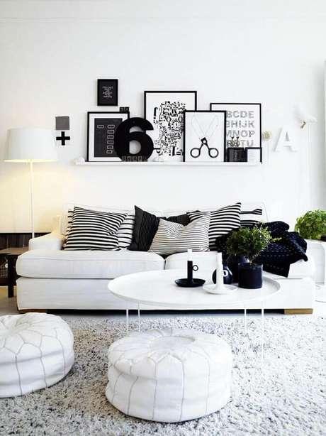 59. Sala minimalista decorada com sofá branco e vários quadros apoiados em prateleira estreita – Foto: Futurist Architecture