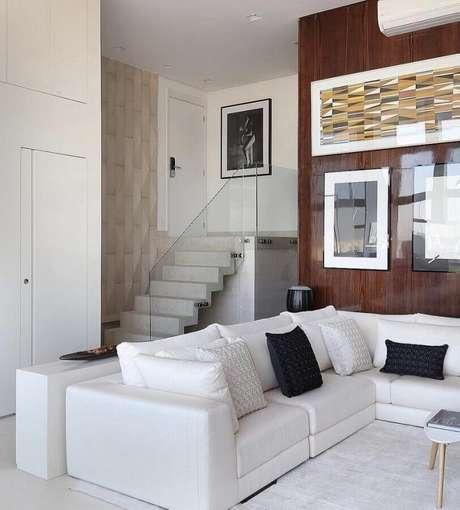 61. Sofá de canto branco para sala com parede revestida de madeira – Foto: Reedcore