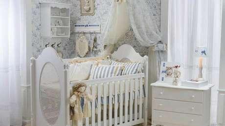 40. Quarto de bebê com berço provençal branco e papel de parede floral azul. Fonte: Sou Mãe