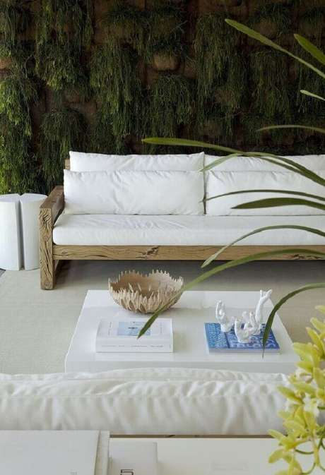 63. Varanda decorada com jardim vertical e sofá branco com base de madeira – Foto: Diego Revolto Arquitetura
