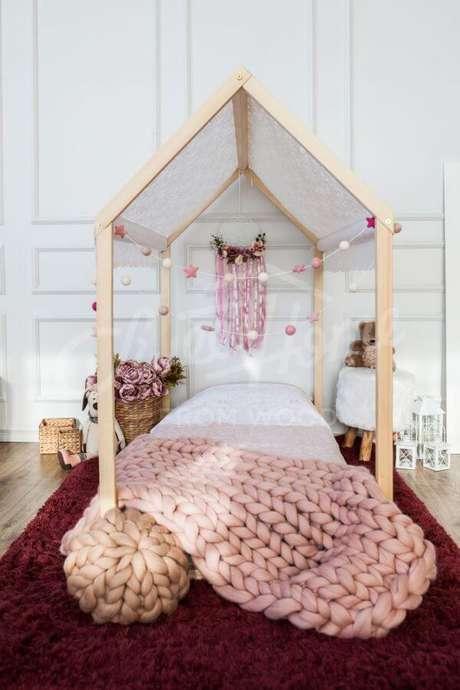 17. Cama casinha de madeira com manta rosa na decoração – Por: Pinterest