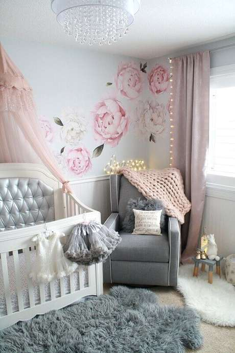 16. Quarto de bebê feminino decorado com adesivo de parede floral e tapete felpudo cinza e branco – Foto: Pinterest