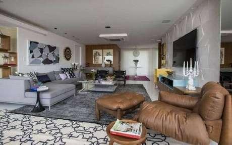 18. Tapete cinza para sala de estar ampla decorada com poltrona de couro – Foto: Rodrigo Maia Arquitetura