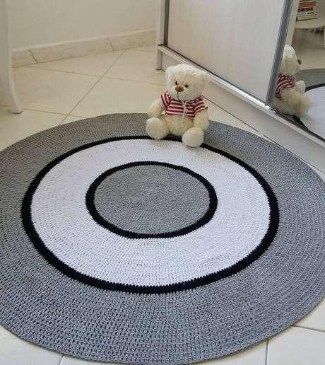 31. Modelo de tapete cinza redondo feito em crochê com círculo branco – Foto: Pinosy