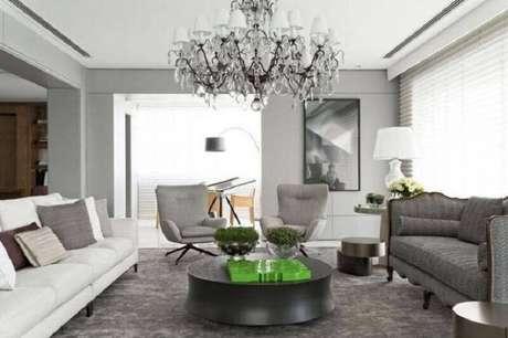 35. Tapete cinza para sala decorada com dois modelos diferentes de sofá e lustre candelabro – Foto: Roberto Migotto