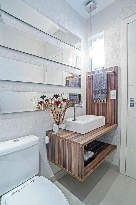 43. A toalha de lavabo escura contrasta bem com a madeira do gabinete. Projeto de Patrícia Azoni