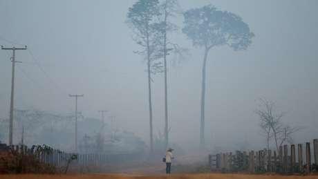 Homem caminha em estrada em Porto Velho em meio à fumaça; ex-presidente afirma que uma parte das queimadas acontecendo atualmente nas florestas é 'proposital'