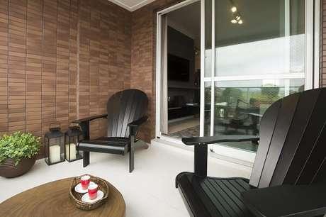 32. Varanda com cadeira de madeira preta. Projeto por Juliana Pippi