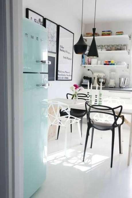 27. Cozinha com cadeiras pretas e brancas e geladeira retrô azul claro – Por: Pinterest