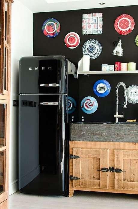 37. Geladeira retrô preta com armários de madeira e parede estampada – Por: Pinterest