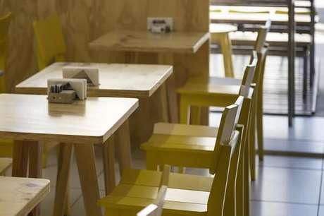 29. Mesa e cadeira de madeira complementam a decoração desse espaço comercial. Projeto por Kali Arquitetura