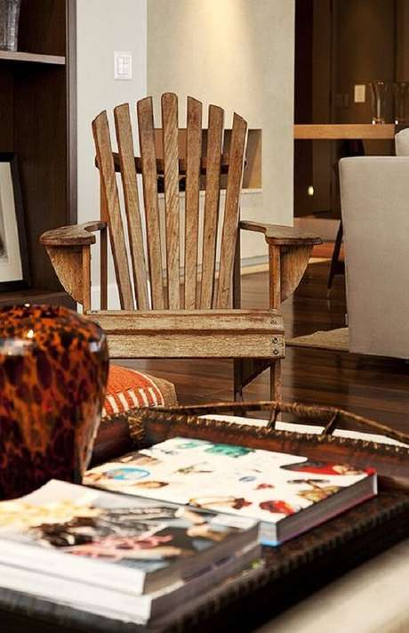 39. Sala de estar com cadeira de madeira e mesa de centro. Projeto por Fernando Piva
