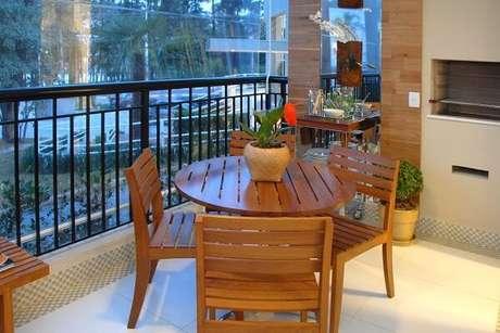 54. Varanda gourmet com mesa redonda e modelo de cadeira de madeira. Projeto por Marel Grupo Factory