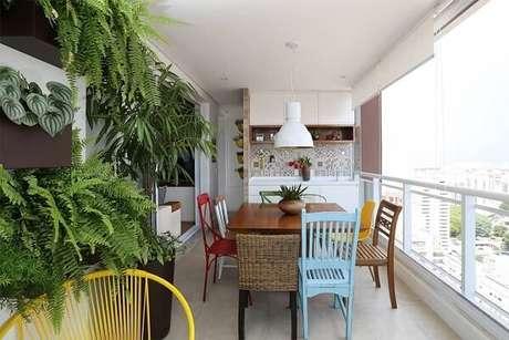 55. Varanda gourmet decorada com mesa e modelo de cadeira de madeira colorida. Fonte: Pinterest