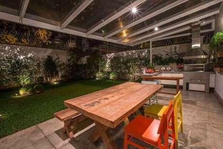56. Varanda gourmet integrada ao jardim conta com mesa e cadeira de madeira colorida. Fonte: Revista Viva Decora