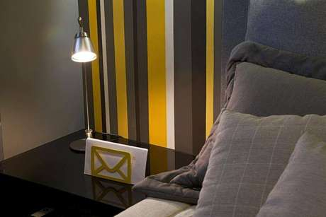 41. O amarelo é uma cor forte, mas que pode ter propriedade sóbrias em um papel de parede listrado. Projeto de Eduarda Corrêa