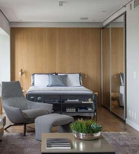 14. Poltrona com puff para quarto de casal cinza com guarda roupa espelhado e parede com revestimento de madeira – Foto: Triplex Arquitetura