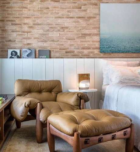 17. Poltrona com puff para quarto com papel de parede de tijolinho – Foto: Paola Ribeiro