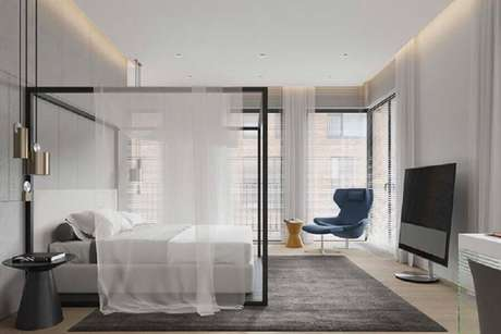 20. Poltrona com puff para quarto de casal amplo com dossel e luminárias modernas – Foto: Pinterest